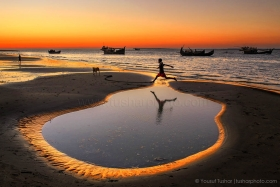 A boy crossing the little pond beside sea beach at Cox's Bazar Dry fishing village, Bangladesh. In the village more than 5000 families engaged with dry fish processing. Their children have no modern toys to paly, so some times they play and making fun by themselves like as jumping on the little pond beside the sea.