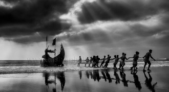 Fishermen Dragging the boat from the sea at bay of Bengal.
