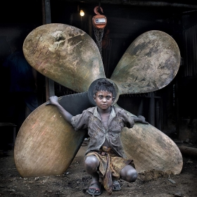 The boy feeling him as butterfly at  Dhaka shipyard where people still making propeller by traditional way.