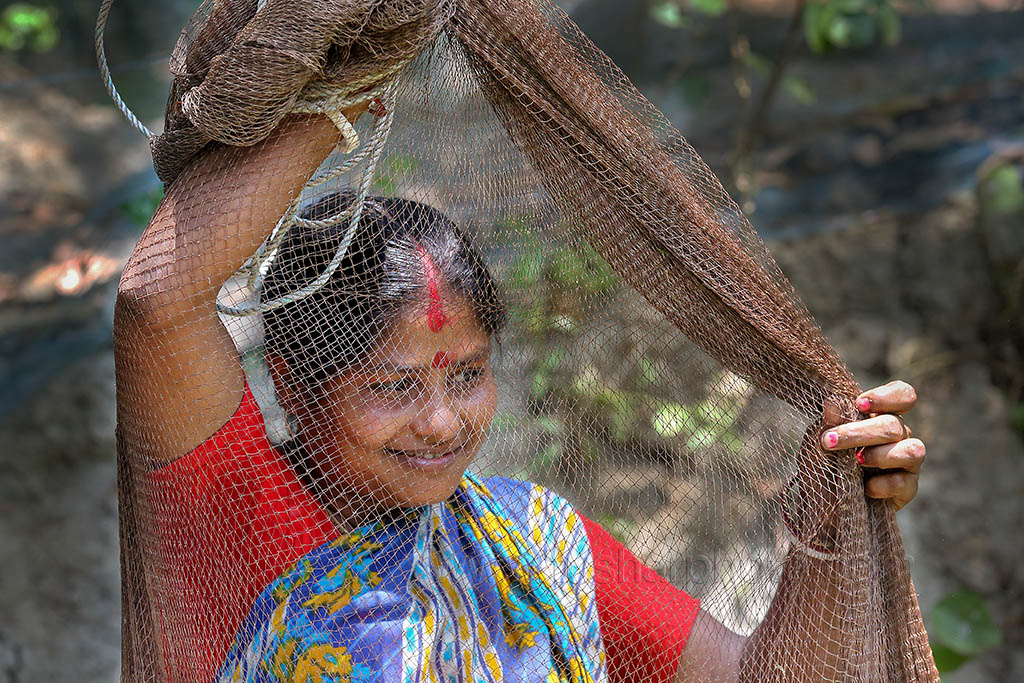 The woman taking preparation to throw fishing net to her pond in Khulna, Bangladesh. Photo by M. Yousuf Tushar. April 18, 2014