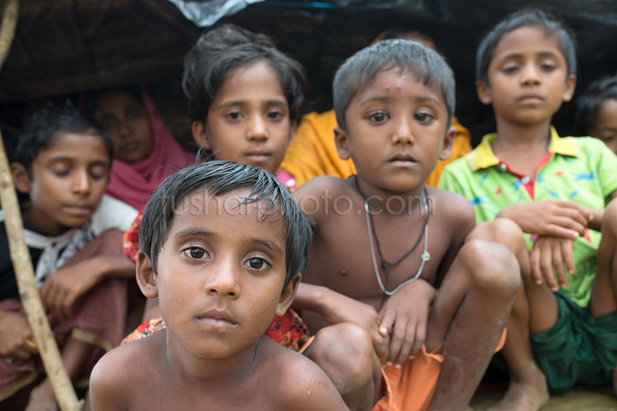 PALONGKHALI, UKHYA, COX'S BAZAR, BANGLADESH- SEPTEMBER 26, 2017: Rohingya children wait for food aid near the Thengkhali makeshift camp in Cox's bazar, Bangladesh. Thousands of Rohingyas still crossing the border between Myanmar and Bangladesh after the Burmese army started an operation against the Rohingyas, by burning and destroying their home in the Rakhine state of Myanmar, as now more than 410,000 Rohingyas crossed the border and the United Nations expect the number rises to 1 million by the end of the year.