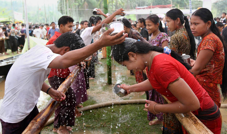Ethnic Rakhain community celebrates water festival. It is a part of their New Year celebration. Young boys and girls throw water to each other to express their love and selecting life partner. The Rakhain boys come across from different places performing music and dance. Then the girls throw water to the boys of their likings. Rakhains of all ages take part in this, as this is their main religious and social festival. Cox's Bazar, Bangladesh.