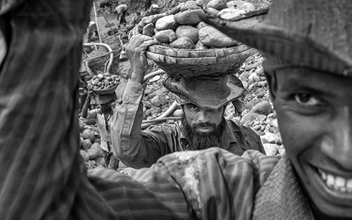 Stone labor carry stone on their head at Jaflong stone quarry field,  hundreds of daily labors continue to migrate to Jaflong in search of jobs at the stone quarry sites, Bangladesh.